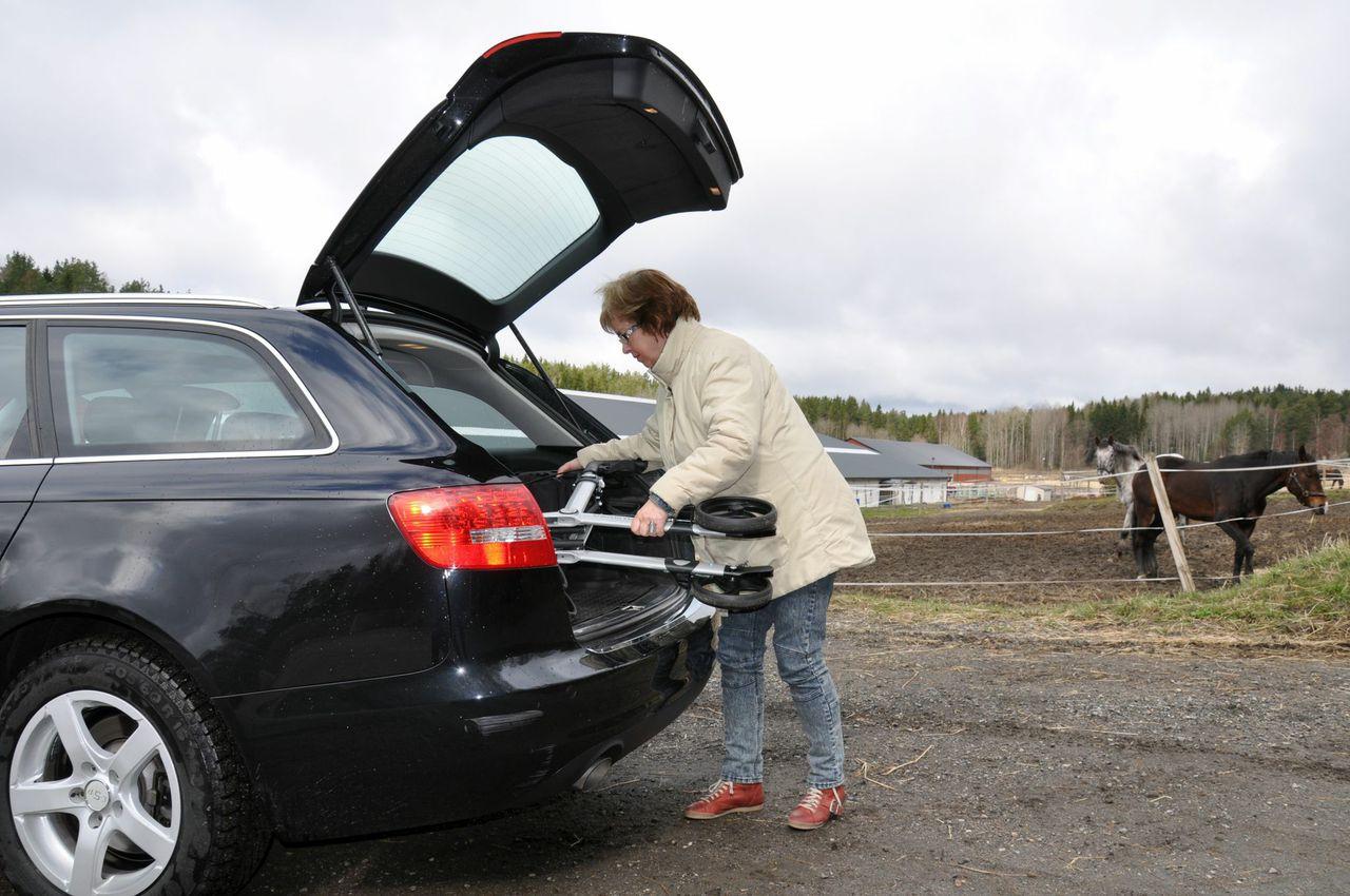 Vrouw legt de opgevouwen Gemino rollator van Sunrise Medical in de auto